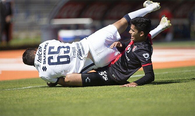 Imagen de dos jugadores peleando por el balón en un Atlas vs Guadalajara. Revisa las mejores cuotas.