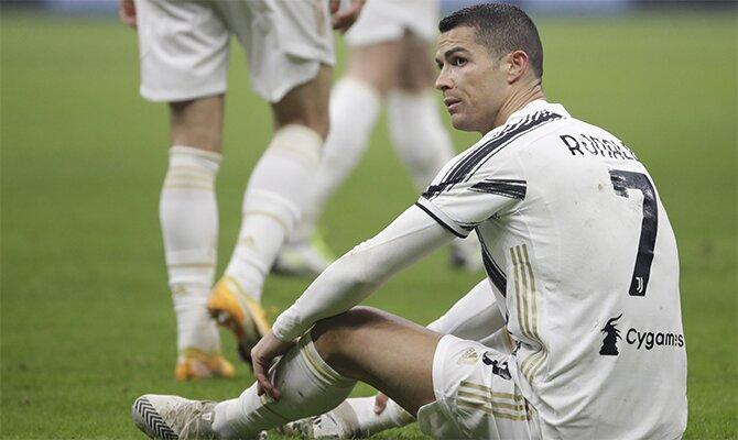 Cristiano Ronaldo sentado sobre el césped. Pronósticos para el Juventus vs Inter de la Serie A.